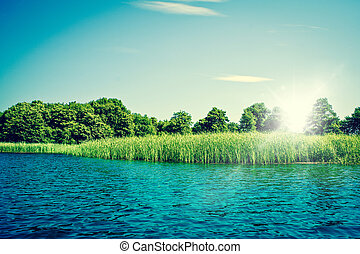 Idyllic lake with blue water and green trees