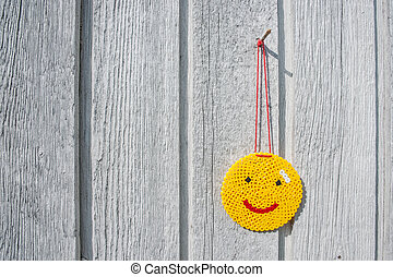 Happy yellow smiley hanging on a wall - High resolution...