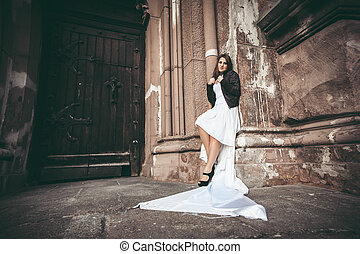Woman in long white dress leaning against ancient wall of...