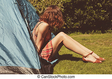 Young woman sitting in a tent