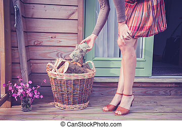 Young woman with logs on porch - A young woman is standing...