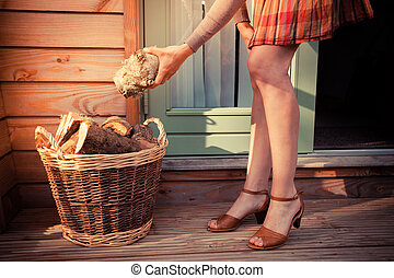 Woman on porch getting logs for firewood - A young woman on...