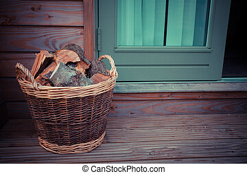Basket of firewood on the porch - A basket of firewood on a...