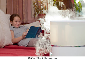 Girl reading book on the background of humidifier - Girl...