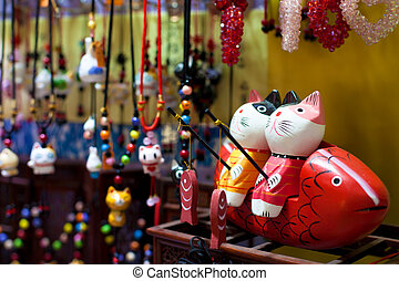 Chinese souvenir shop - Two wooden toy cats fishing in a...