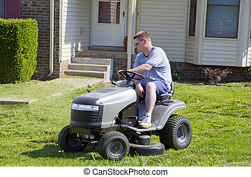 Active Man Mowing lawn and Landscaping - Man on lawn mower,...