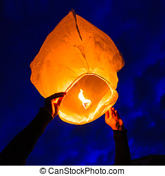 Man holds a chinese lantern as it begins to float, England