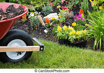 Wheelbarrow alongside a newly planted flowerbed with...