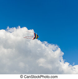 colorful kite flying high in the sky with a cloud