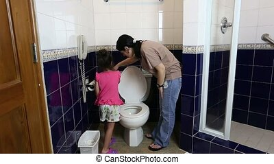 mother teaching her baby to use the toilet