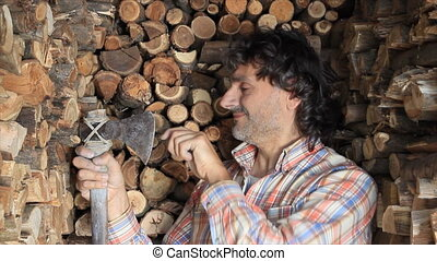 retro woodcutter - smiling man sharpening his axe