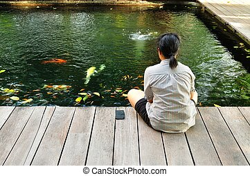 Girl Sitting beside the Fancy Carp Pond - Girl relax by...