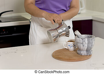 Woman pouring coffee from a percolator into a cup on a...
