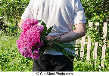 close up of man back with peony in hand - close up of man...