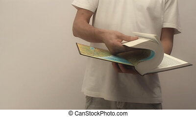 Bible, - young man holding a bible scrolls. camera movement