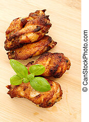 Deep dried chicken wings on a bamboo cutting board with...