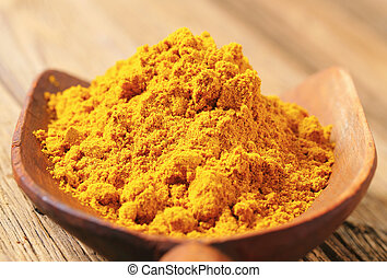 Curry powder - Heap of curry powder on a wooden scoop