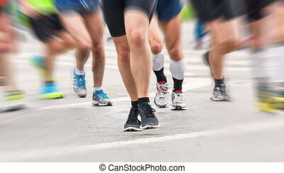 detail of the legs of runners at the start of a marathon...