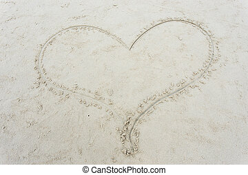 heart drawn on sand at beach