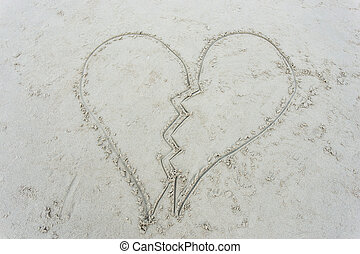 broken heart drawn on sand at beach