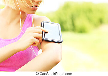 Fit woman with phone - Close up of phone over fit running...