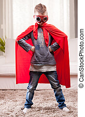 red cloak kid livingroom superhero - a little kid playing as...