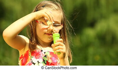 Girl child kid blowing soap bubbles - Summer. Girl child kid...