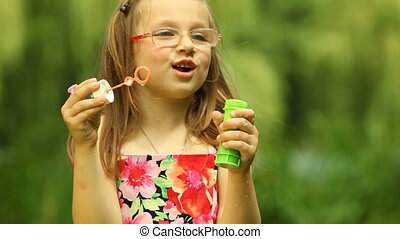 Girl child kid blowing soap bubbles