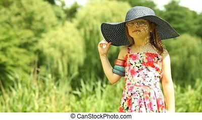 Girl child kid taking straw hat off - Summer. Little girl...