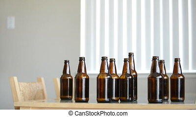 Drunk man sits at table with beer bottles