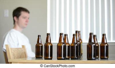 Drunk man leaves table of empty beer bottles