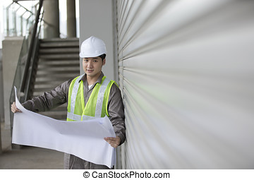 Asian industrial engineer at work looking at plans. -...