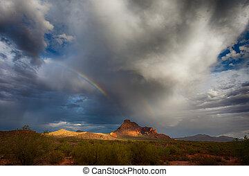 Rainbow Over Mountain - A rainbow forms over a desert...