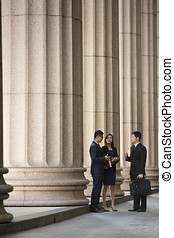 Asian business colleagues outside a Colonial building -...