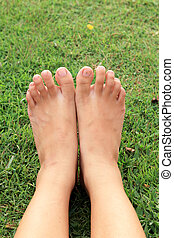 Barefoot on a green lawn.