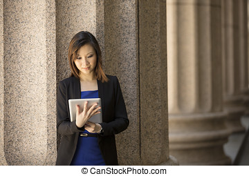 Asian businesswoman outside Colonial building using tablet....