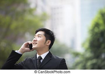 Chinese business man using a smartphone. - Chinese business...