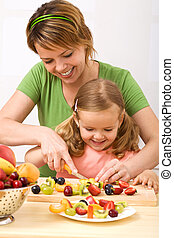 Making fruit salad is healthy and fun - Little girl and her...