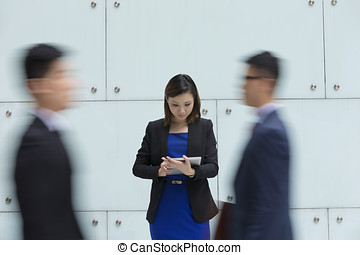Asian businesswoman using tablet surrounded by people...