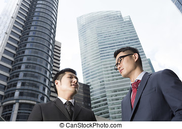 Two Chinese business men in modern Asian city Asian...
