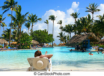 tropical pool bar - woman sitting poolside holding a straw...