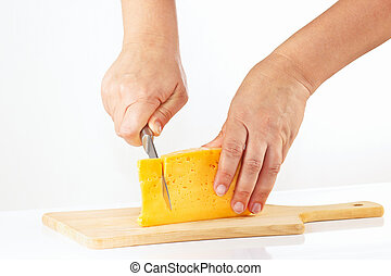 Hand with a knife sliced cheese on a white background