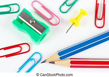 Pencil, paperclips, sharpener and pushpin on white desktop...
