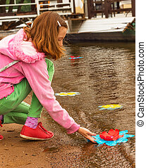 Girl near a river - The girl starts paper flower on the...