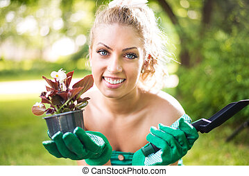 Woman Planting flowers - Portrait of Smiling young woman...