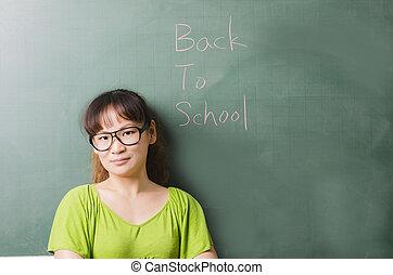 Beauty teacher standing next to a blackboard