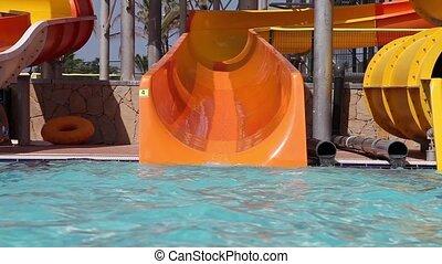Water slide - Little girl sliding down on water slide in...