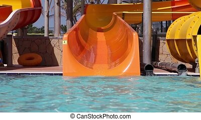 Water park - Grandpa with grandson sliding on water slide in...