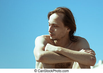 Shirtless man over clear blue sky - Shirtless man sitting on...