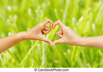 Hand make heart shape framing on green nature background